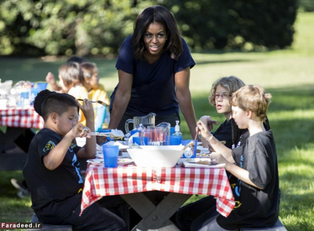 U.S. first lady Obama talks to local elementary school students after picking vegetables with them during the annual fall harvest of the White House Kitchen Garden in Washington