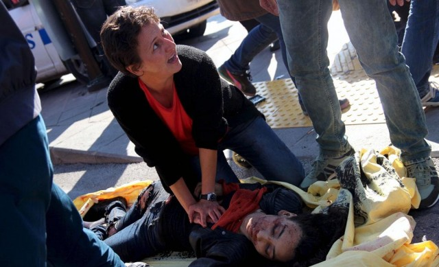 "ATTENTION EDITORS - VISUAL COVERAGE OF SCENES OF INJURY OR DEATHA woman helps an injured woman after an explosion during a peace march in Ankara, Turkey, October 10, 2015. At least one explosion shook a road junction in the centre of the Turkish capital Ankara on Saturday, causing many casualties including fatalities, local media said. The state-run Anadolu Agency said there were reports that the blast was caused by a suicide bomber, but the source of those reports was unclear. The blast occurred ahead of a planned ""peace"" march to protest against the conflict between the state and Kurdish militants in southeast Turkey. Earlier media reports had said there were two explosions. REUTERS/Tumay Berkin       TPX IMAGES OF THE DAY"