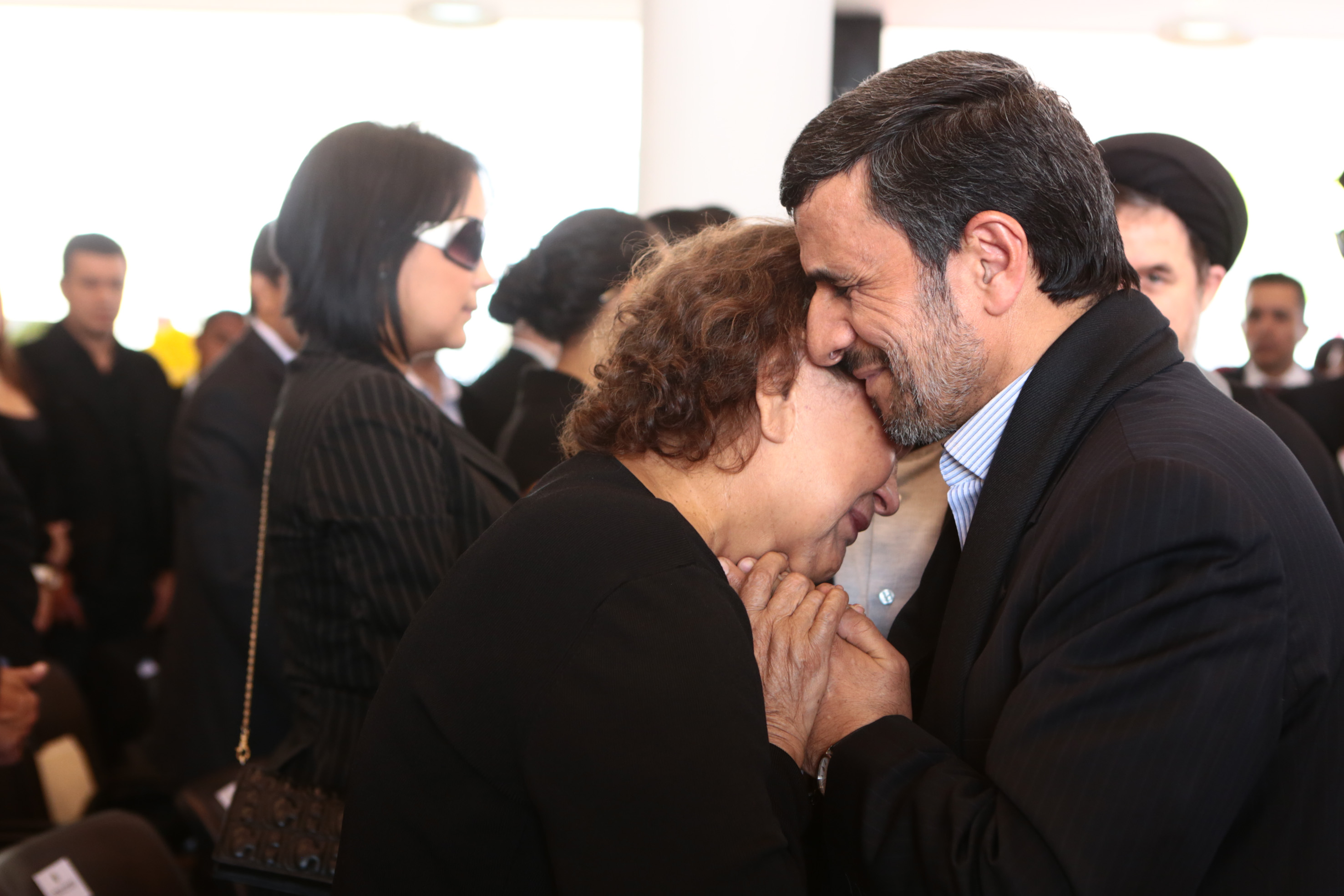 In this photo released by Miraflores Press Office, Iran's President Mahmoud Ahmadinejad comforts Elena Frias next to the flag-draped coffin of her son, Venezuela's late President Hugo Chavez, during the funeral ceremony at the military academy in Caracas, Venezuela, Friday, March 8, 2013. Chavez died on March 5 after a nearly two-year bout with cancer.  He was 58.  (AP Photo/Miraflores Press Office)